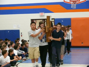 Students from St. Veronica CES in Woodbridge carry the Walk of Faith cross into their school's gym prior to a special liturgy to mark the pilgrimage.